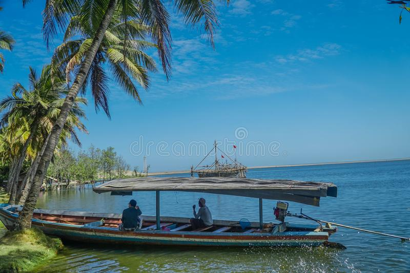 Sukabumi, West Java, Indonesia, September 7th 2018 : The men were talking on a boat that was leaning by the beach. Scenic, thailand, wild, dawn, sunset stock image