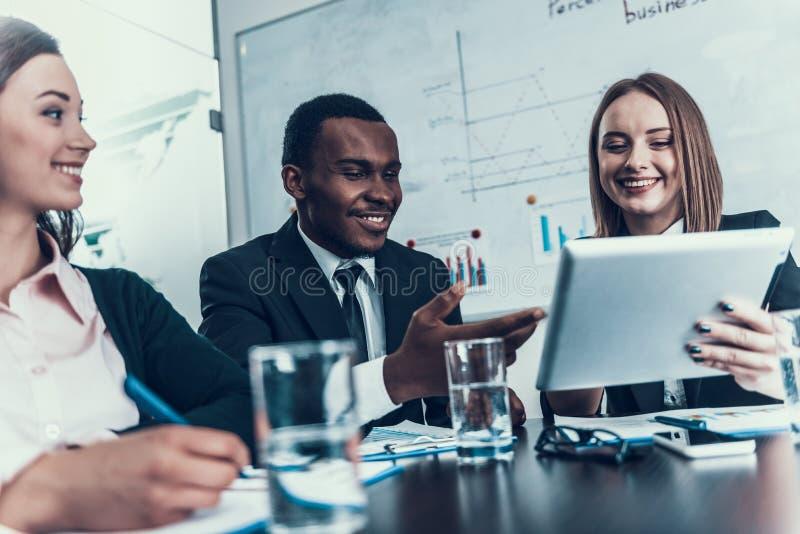 Sukces uśmiechnięta kobieta pokazuje coś czernić biznesmena przy biznesowym spotkaniem na komputerowej pastylce zdjęcia royalty free