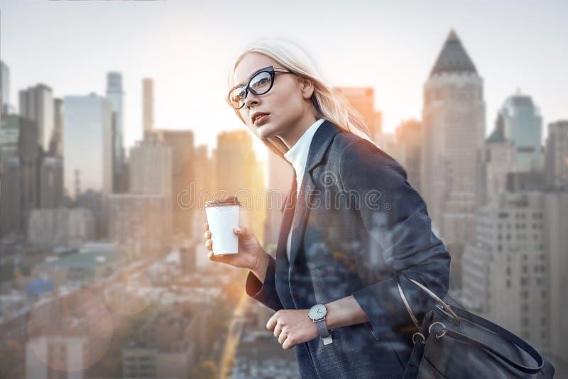 sukces young Boczny widok trzyma filiżanka kawy ufna kobieta podczas gdy stojący outdoors z nowożytnym biurem fotografia royalty free