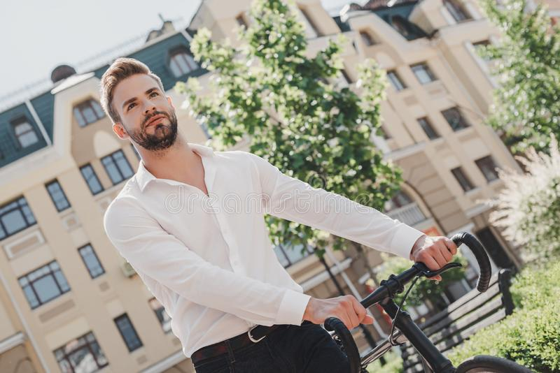 Sukcesu zazwyczaj komes tamto które są zbyt ruchliwie być przyglądający dla go Młoda brązowowłosa mężczyzna pozycja w parku z a zdjęcia royalty free