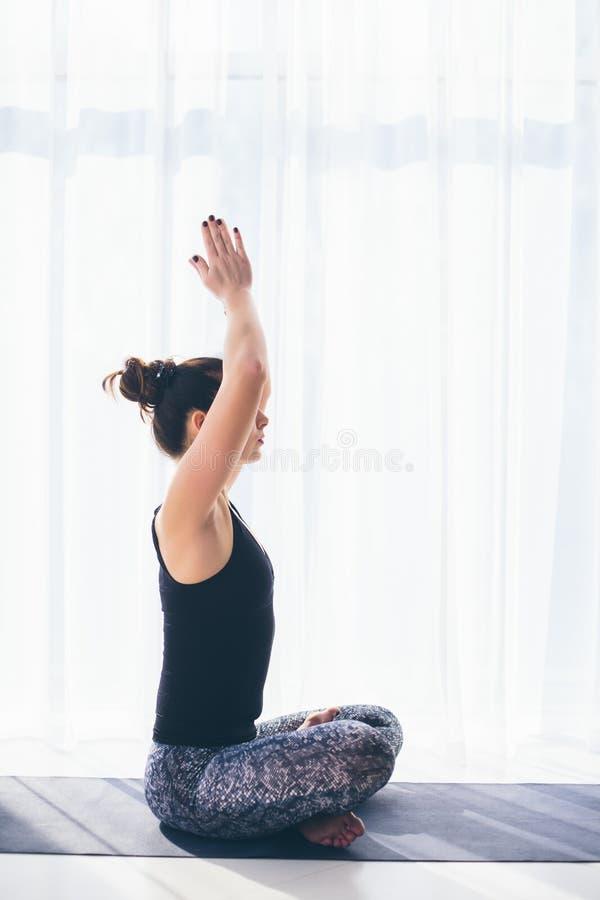 Sukhasana De mooie praktijk van de yogavrouw op een achtergrond van de opleidingszaal royalty-vrije stock afbeelding
