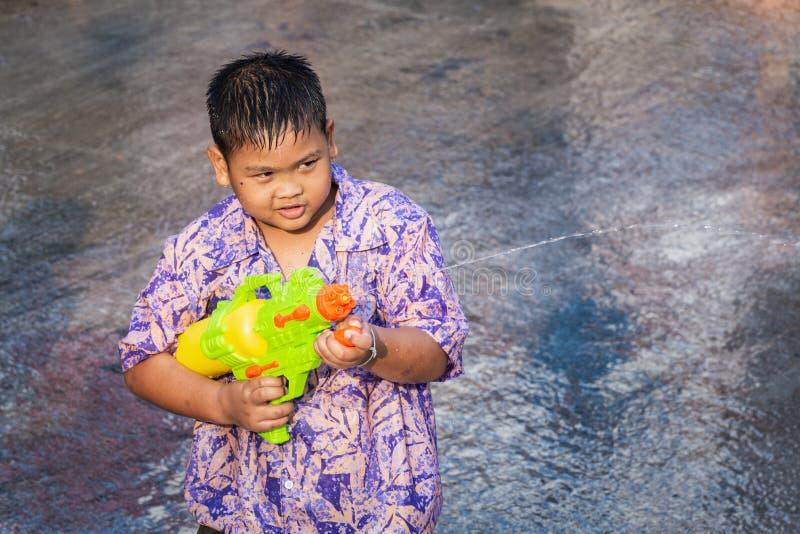 Sukhothai,泰国- 2019年4月15日:与水枪的泰国男孩射击在新年Songkran水节日期间 免版税库存照片