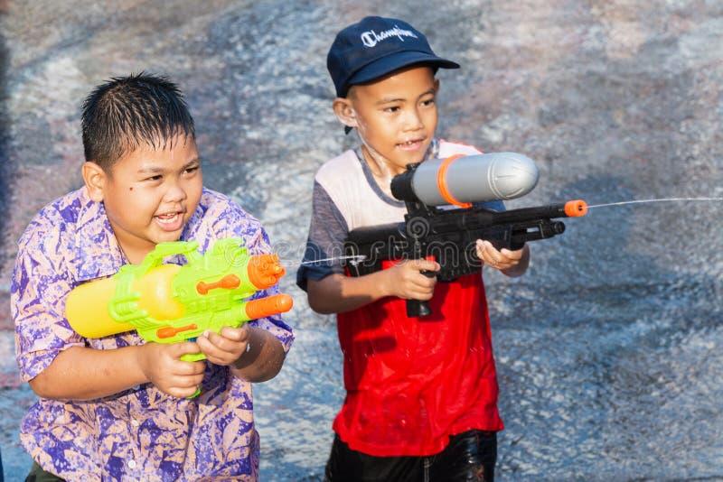Sukhothai,泰国- 2019年4月15日:射击与水枪的泰国孩子在新年Songkran水节日期间 免版税库存图片