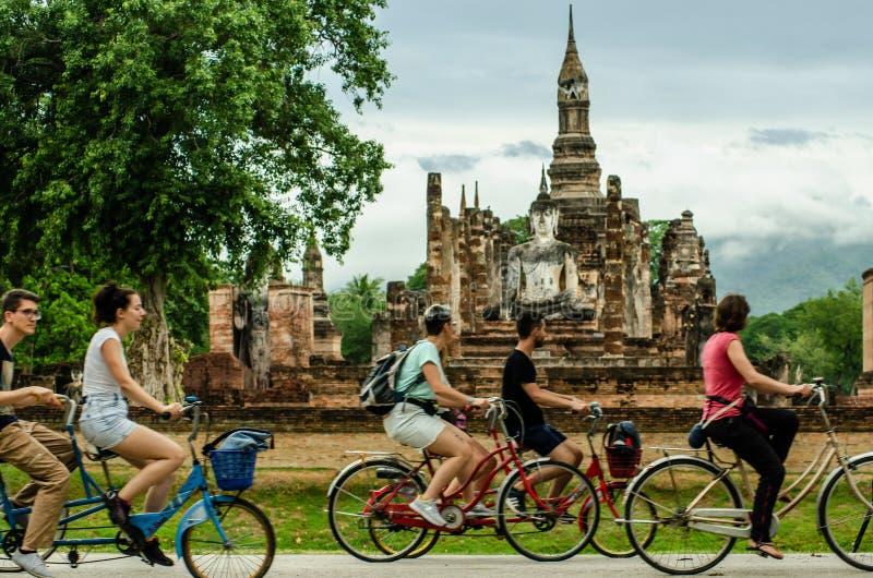 SUKHOTHAI, TAILANDIA – 25 DE JULIO DE 2019: Ciclo turístico alrededor de los Antiguo-restos que muestran la evolución a partir de imagen de archivo libre de regalías