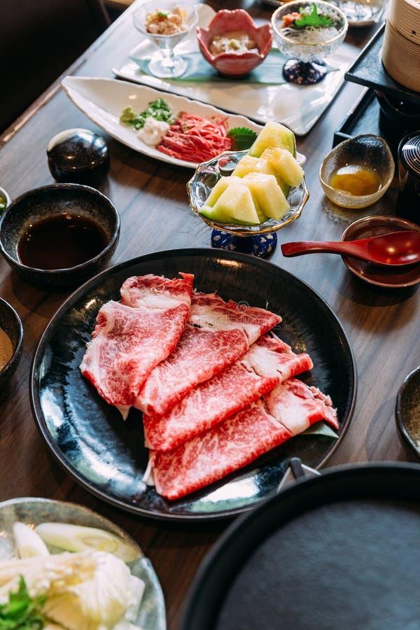 Sukiyaki ajustou incluir a carne rara de Wagyu A5 das fatias na placa preta com melão japonês foto de stock royalty free