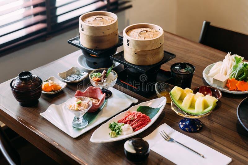 Sukiyaki ajustou incluir a carne rara de Wagyu A5 das fatias, o molho de Shoyu, o melão japonês e os vegetais fotos de stock