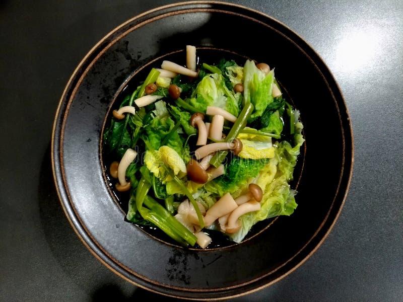 Sukiyaki in una ciotola ceramica nera sulla tavola nera funghi, cavoli bianchi e ipomee fotografia stock