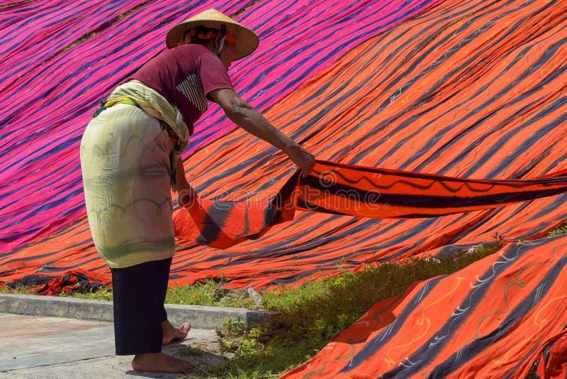 Sukoharjo, Indonesië, 11 januari 2018 Werknemers zijn bezig met het drogen van de badstof aan de oevers van de Solo Be stock afbeelding