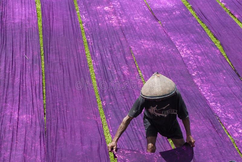 Sukoharjo, Indonesia, 11 de enero de 2018. Los trabajadores están llevando a cabo el proceso de secar la tela de la playa a orill imagen de archivo libre de regalías