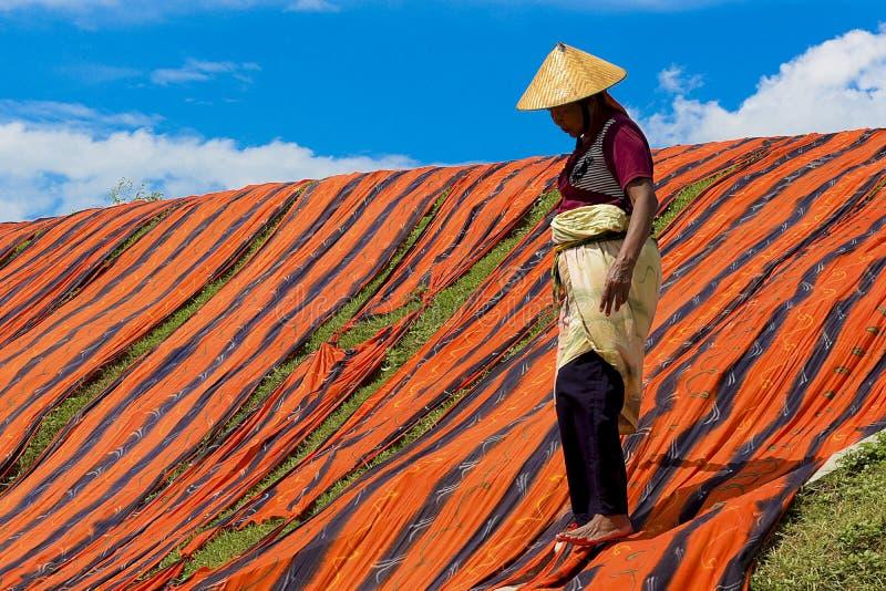 Sukoharjo, Indonesia, 11 de enero de 2018. Los trabajadores están llevando a cabo el proceso de secar la tela de la playa a orill imagen de archivo