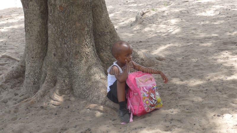 Sul - criança africana das esperas de uma escola primária para o ônibus escolar após a classe imagem de stock royalty free