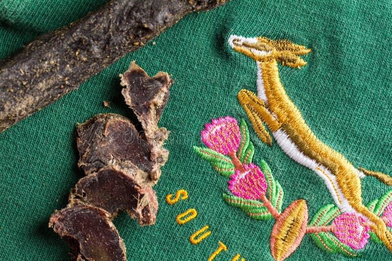 Sul - jérsei africano do rugby da gazela cerca de 1995 com fatias de carne seca do veado, petisco típico de África do Sul especia foto de stock