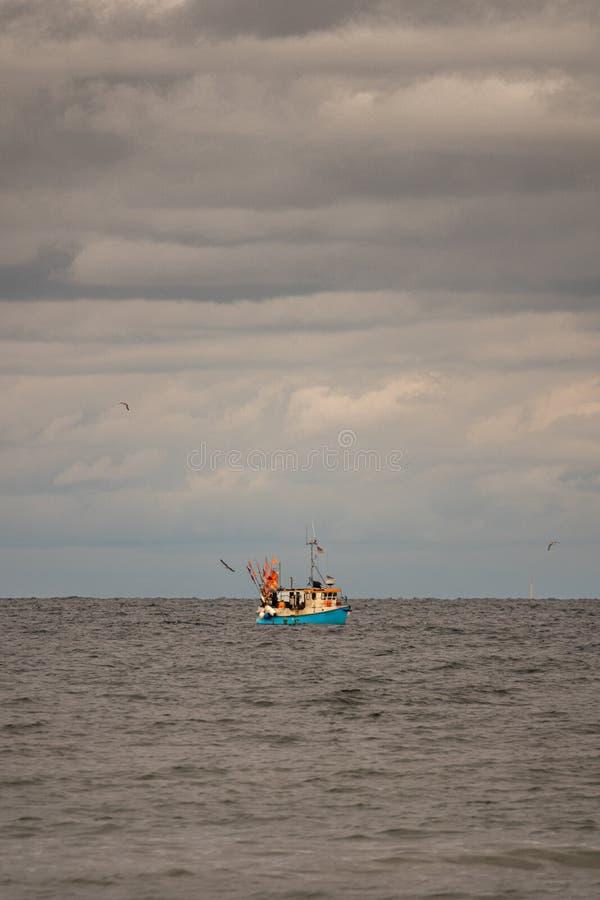 Sul mare galleggia un peschereccio, circondato da molti gabbiani e il cielo è pieno di nuvole immagini stock