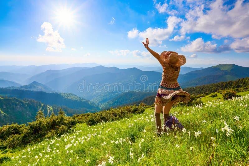 Sul prato inglese in montagne abbellisce la ragazza dei pantaloni a vita bassa in vestito, calze e cappello di paglia immagini stock libere da diritti