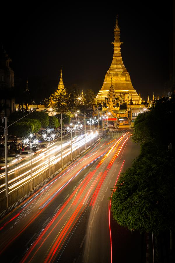 Sule Pagoda by night in downtown Yangon. Brightly light golden pagoda with light trails from traffic in the foreground royalty free stock photos