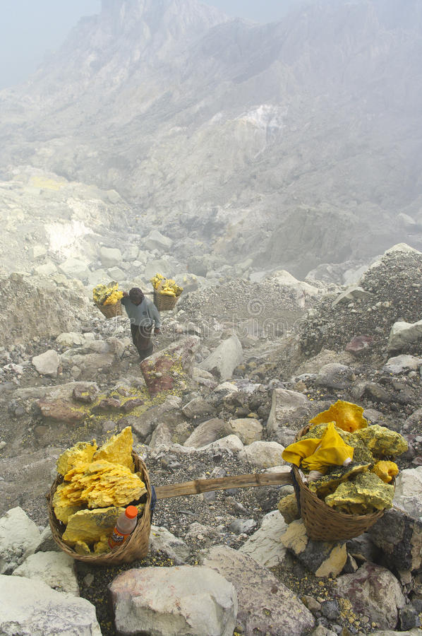 Sulfuro que lleva del trabajador dentro del cráter de Ijen foto de archivo