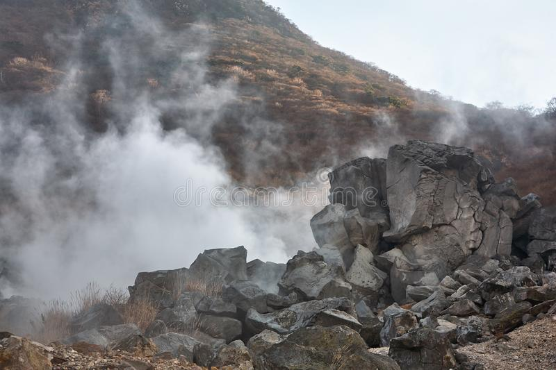 The sulfurous fumes of Owakudani  Valley.  Hakone area. Honshu. Japan. Powerful outbursts of fumes and sulfur among the rocks in the  Owakudani  Valley.  Hakone royalty free stock photo