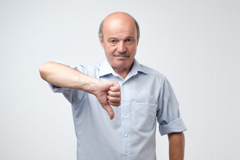 Sulking mature caucasian man showing his dislike and disappointment with thumbs down in the foreground. royalty free stock images