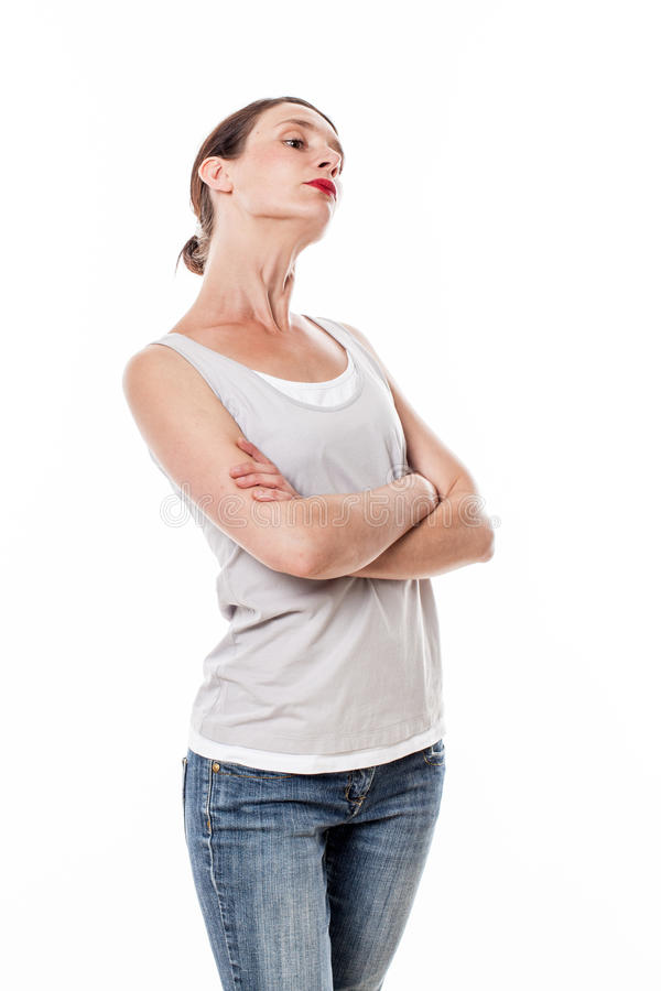 Sulking woman with arms folded posing with chin up for arrogance. Attitude concept - sulking young woman with arms folded posing with chin up for arrogance or royalty free stock photos