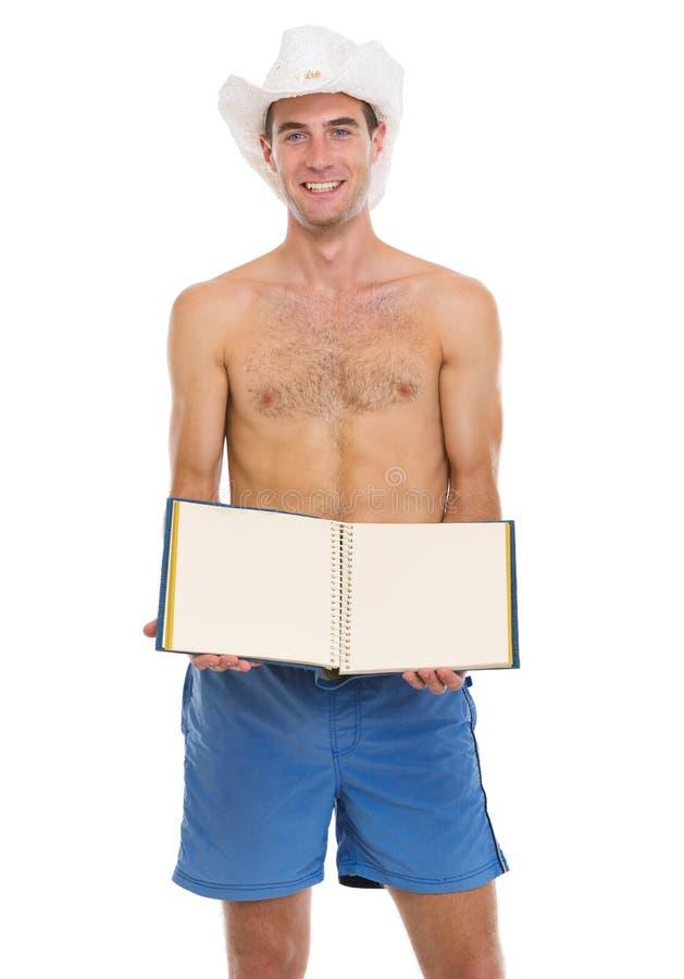 Sull'uomo di vacanza in cappello della spiaggia che mostra phot in bianco immagine stock