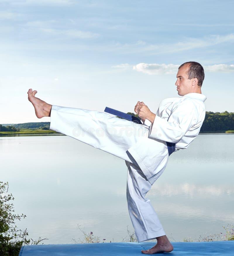 Sulla costa del lago l'atleta batte una gamba di scossa in avanti fotografia stock libera da diritti