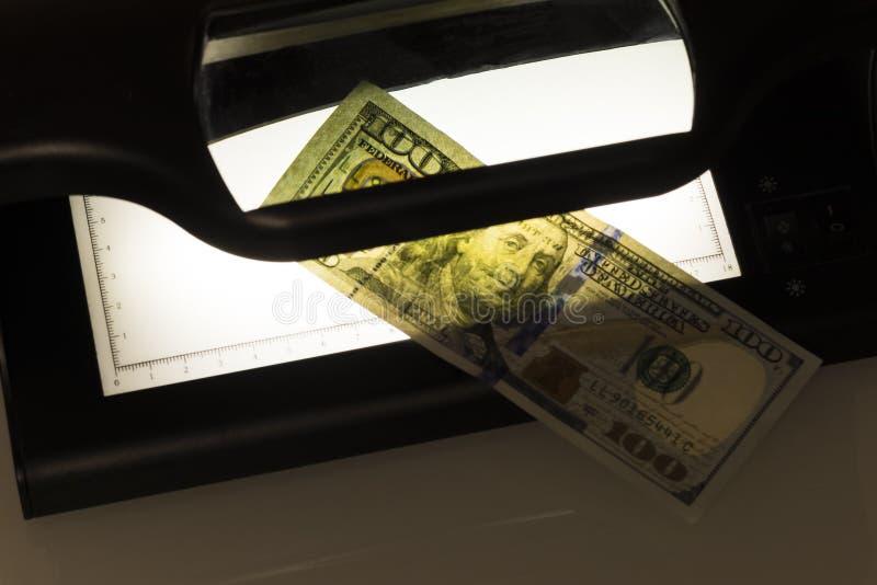 Sulla foto ? cento dollari Noi banconote Attrezzatura per ispezione approfondita di soldi Controllo della fattura nell'ultraviole fotografia stock