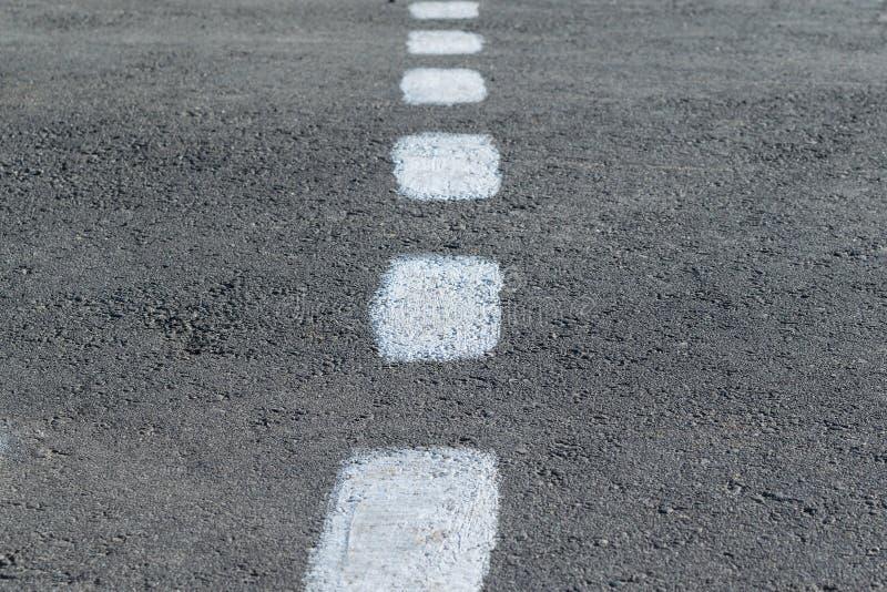 Sulla marcatura della pavimentazione Linea bianca intermittente approssimativa fotografia stock