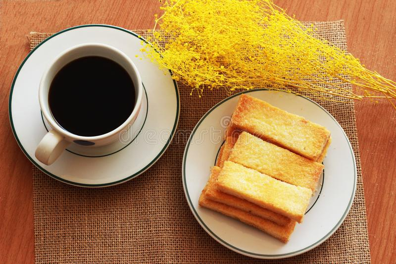 Sulla tavola, c'è un caffè nero nel vetro, un panino croccante immagini stock libere da diritti