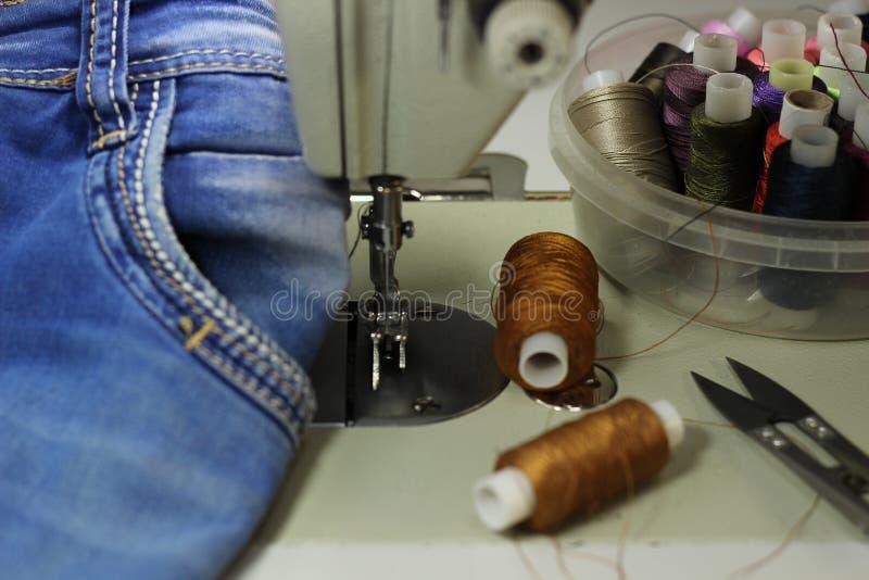 Sulla tavola dei tessuti del denim di bugia della macchina per cucire, primo piano, fotografia stock libera da diritti