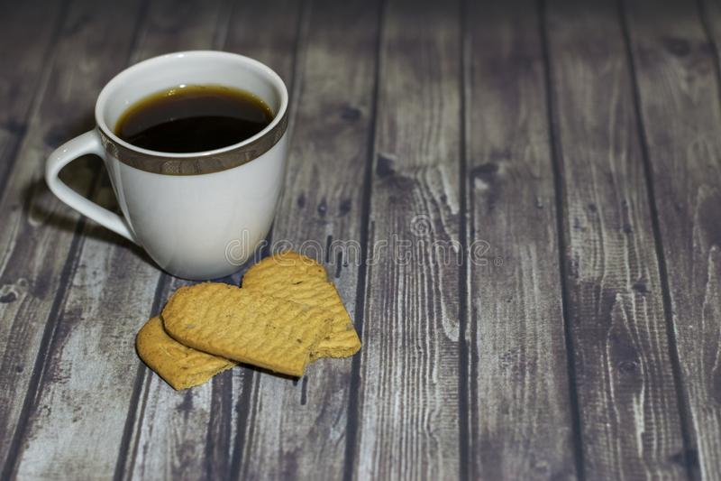 Sulla tavola di legno è una tazza bianca, un biscotto rotto del cereale immagine stock
