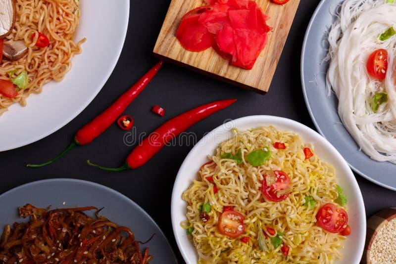 Sulla tavola, sui piatti dai tipi differenti di tagliatelle, sul peperoncino rosso e sullo zenzero Vista da sopra fotografia stock