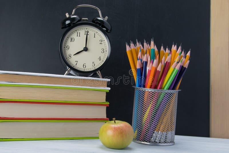 Sulla tavola un la pila di libri con una sveglia sulla cima, una rottura dello spuntino fotografie stock libere da diritti