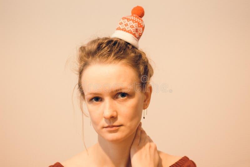 Sulla testa della ragazza sono i capelli legati in un panino su cui un cappello con i modelli di Natale è portato immagine stock libera da diritti