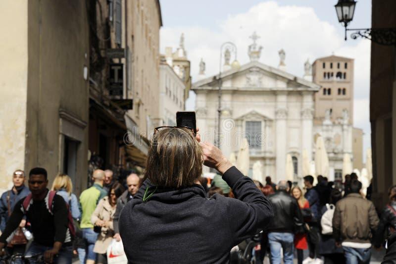 Sulla uomo Primo piano del turista strada Mantova, telefono Di Piazza Sordello con IL foto prendendo Mantova, Ιταλία στοκ εικόνες