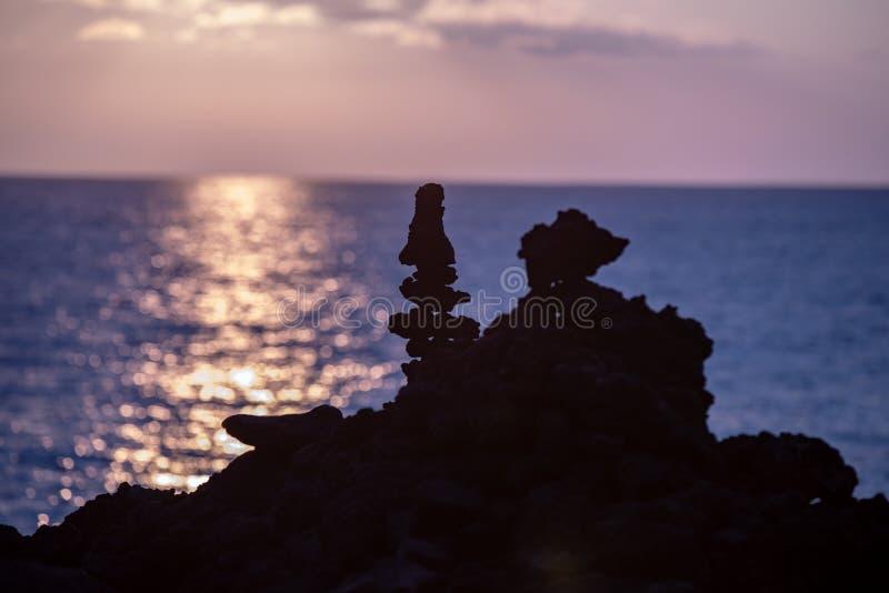 Sulla vista vicina delle siluette delle formazioni rocciose alte della lava contro il tramonto sopra l'oceano Pacifico immagine stock