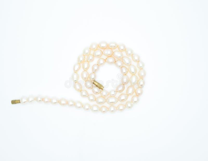 Sulle bugie di un fondo di bianco una collana rosa della perla sul collo fotografia stock libera da diritti