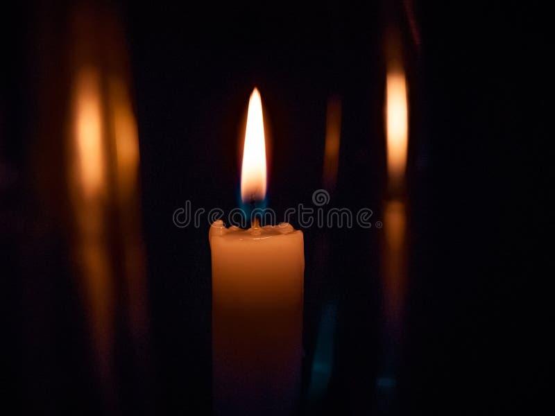 Sulle candele gialle luminose di un fondo nero, su una festa o su un chur fotografie stock libere da diritti