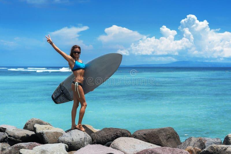 Sulle rocce, sullo sfondo del mare e del cielo nuvoloso, sorge una donna burundese. Indossa bikini blu, occhiali da sole fotografie stock