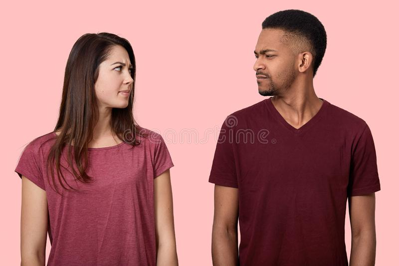 Sullen displeased multiethnic lady and male looks with discontent at each other, frown faces, dont like something, wear t shirt, stock photo