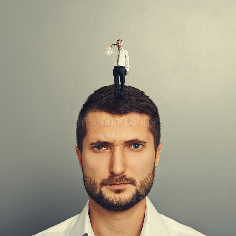 Sullen man with small man on the head. Over grey background stock photography