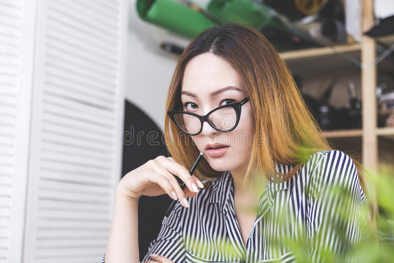 Sultry asian woman at workplace stock photo