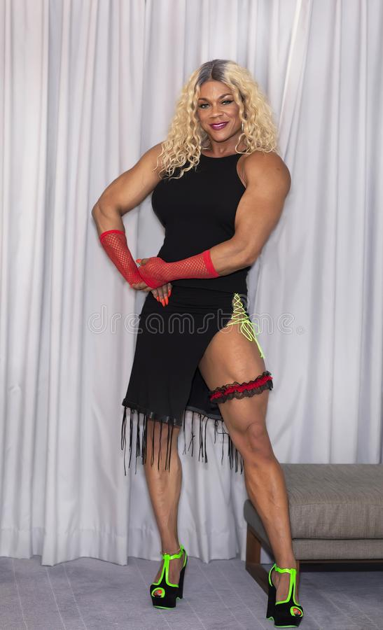 Kim Buck, Enticing Woman Bodybuilder. Sultry female professional bodybuilder Kim Buck from Georgia strikes an inviting pose. In this photo Buck is in her off royalty free stock images