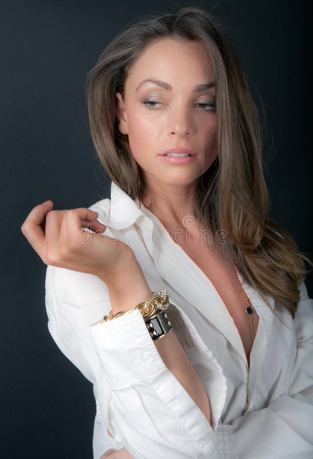 Sultry Woman. An image of a gorgeous woman in a white button down shirt royalty free stock photography
