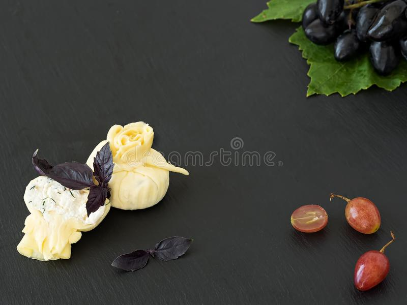 Suluguni cheese with ricotto is located on a black stone plate, next to grape berries and a bunch of ripe grapes on a leaf. Black. Stone background. Top view stock photos