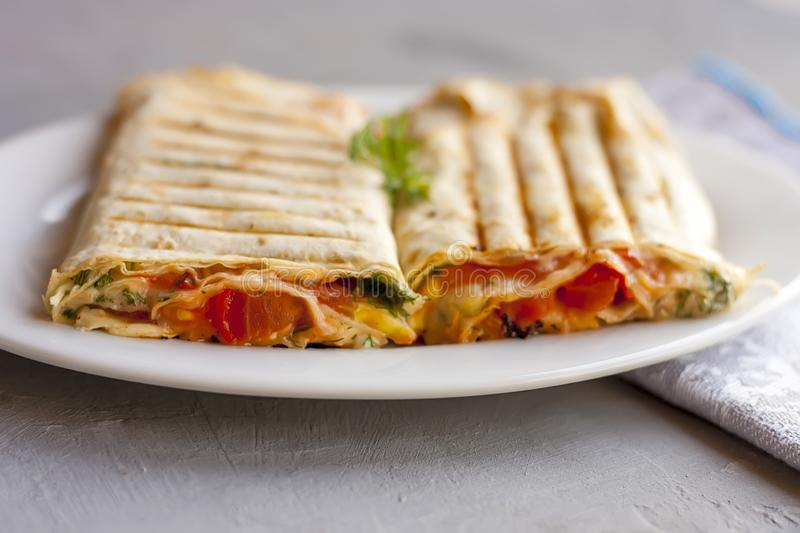 Suluguni in pita bread with greens and tomatoes on a white plate stock photography