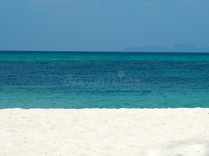 Sumário borrado no fundo da praia do oceano do verão das férias Céu azul claro, mar tropical bonito, água azul e whit agradável d fotografia de stock