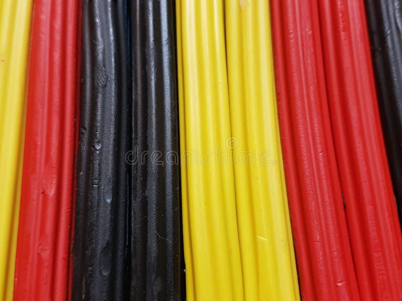 sumário com as barras do plasticine na cor preta, amarela e vermelha, no fundo e na textura imagens de stock