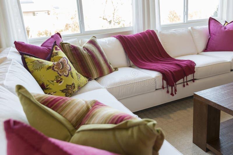 Sumário de convidar a área colorida da sala de visitas do sofá imagens de stock royalty free