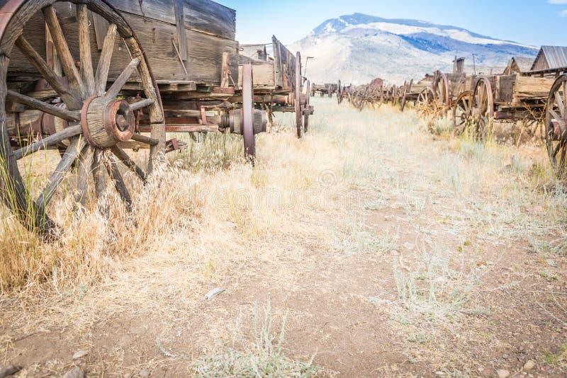 Sumário de vagões de madeira antigos e das rodas de vagão velhas resistidas imagens de stock