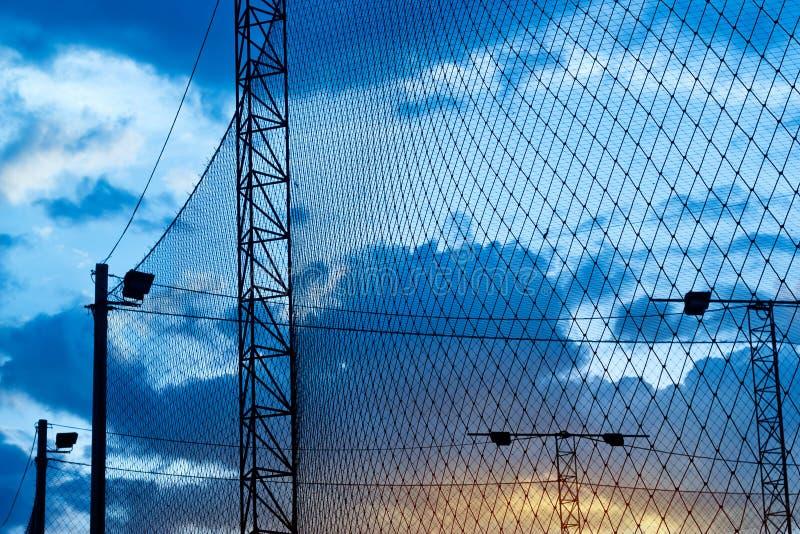 Sumário, silhueta colorida da rede em torno do futebol do campo no por do sol azul fotos de stock